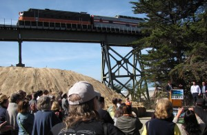crowd watching train on bridge
