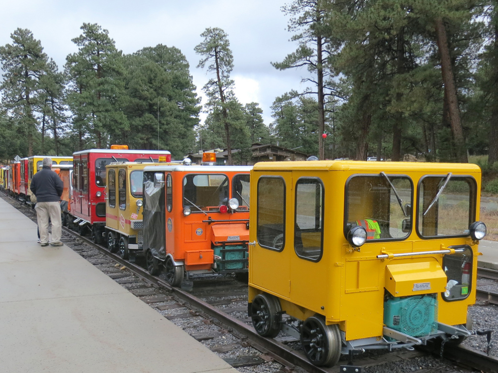 Many railcars aka speeders, lined up at a railroad platform